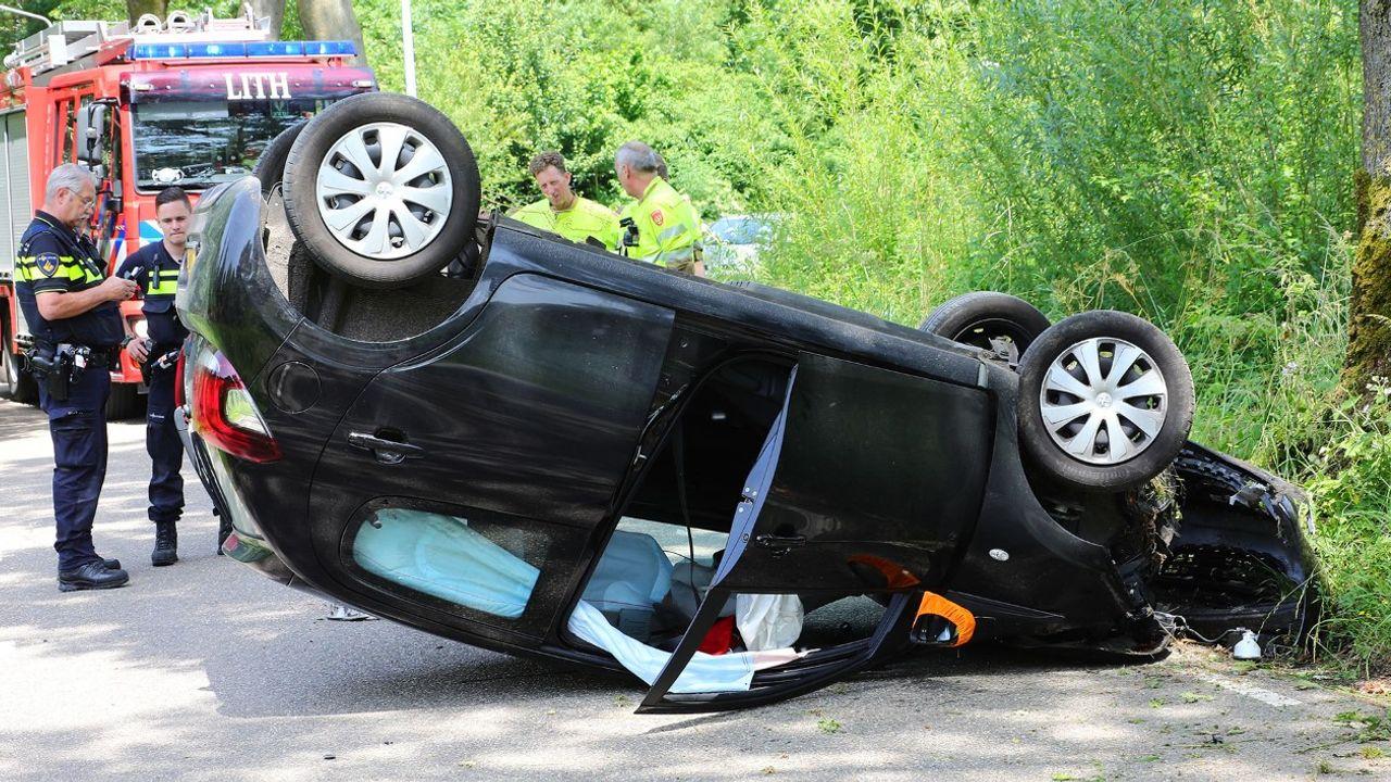 Auto over de kop na botsing met boom in Lithoijen