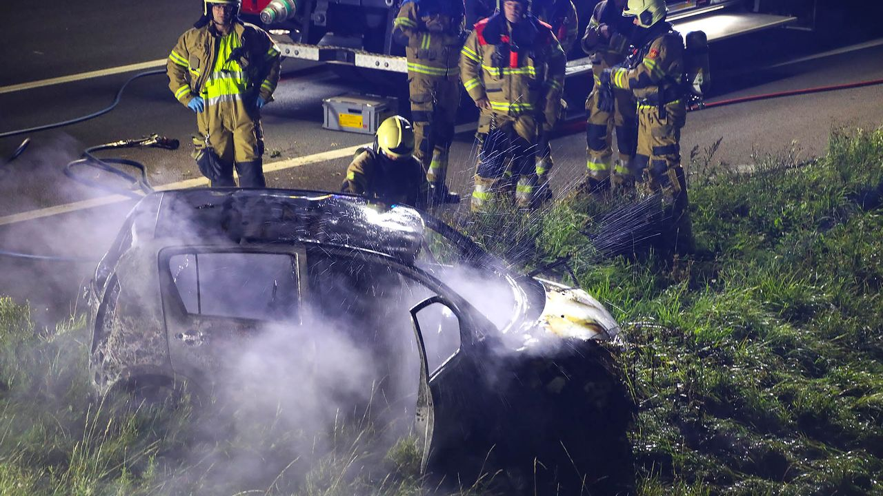 Volledig uitgebrande auto in berm snelweg